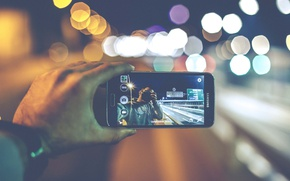 Wallpaper camera, bokeh, hand, globes, Samsung, lights, reversed, selfie, cell phone, urban scene